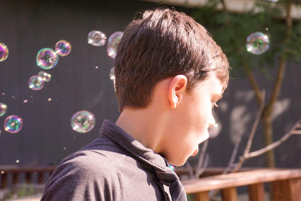 boy in black crew neck shirt blowing bubbles