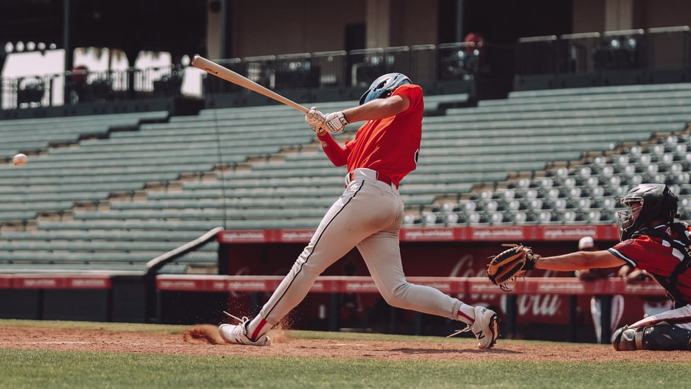 woman in red jersey shirt and white shorts holding baseball bat