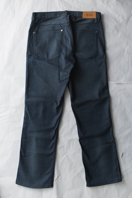 blue denim jeans on white textile