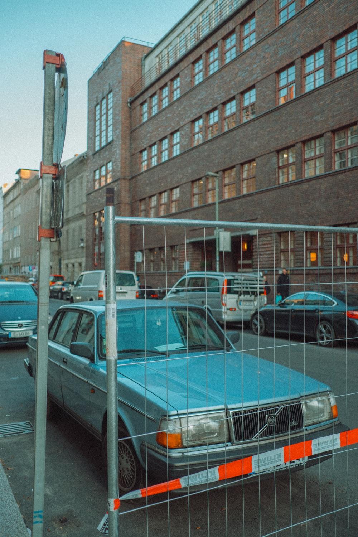 blue sedan parked beside gray suv during daytime