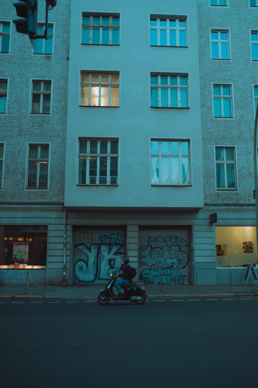 man in black jacket riding motorcycle near white concrete building during daytime