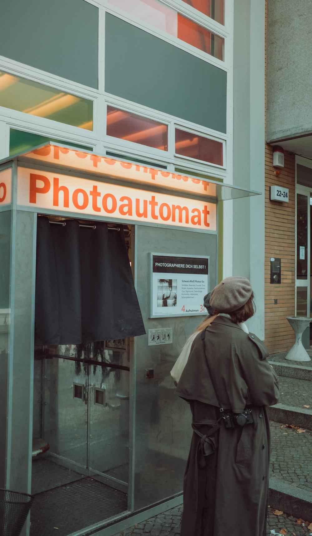 person in gray coat standing near glass window