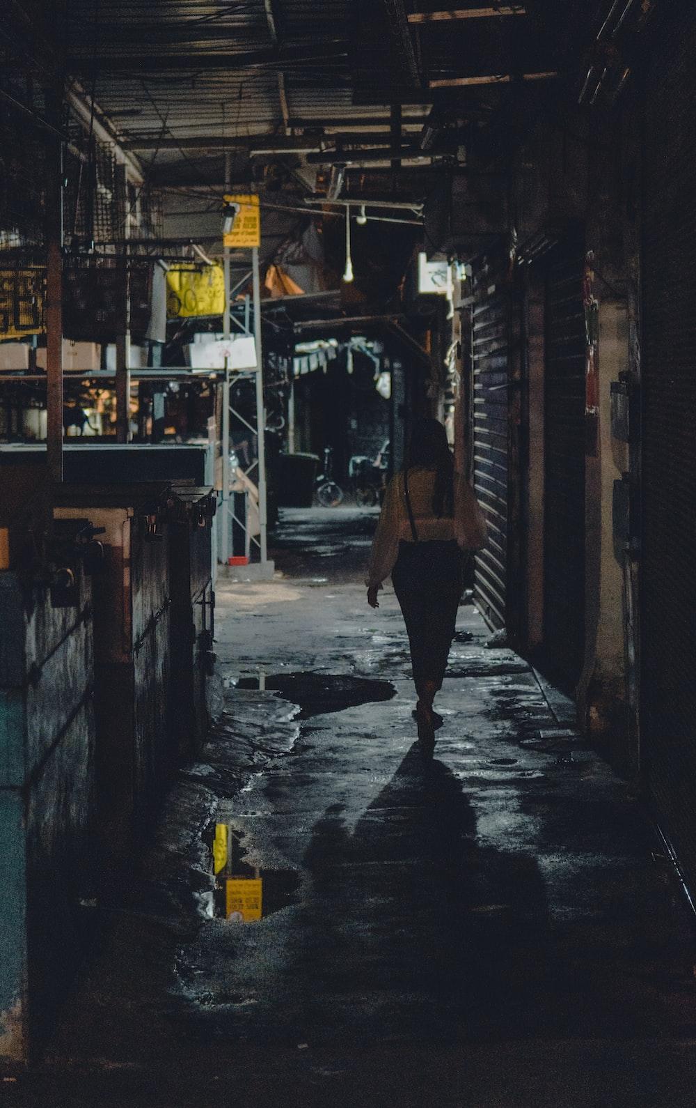 woman in black tank top and black skirt walking on sidewalk during night time