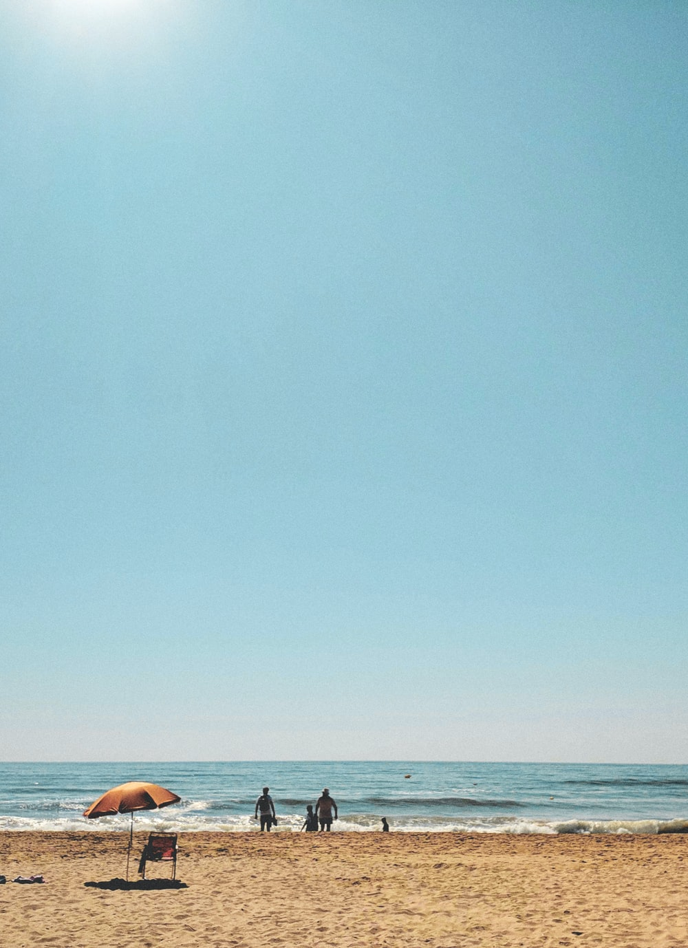 2 person lying on beach during daytime