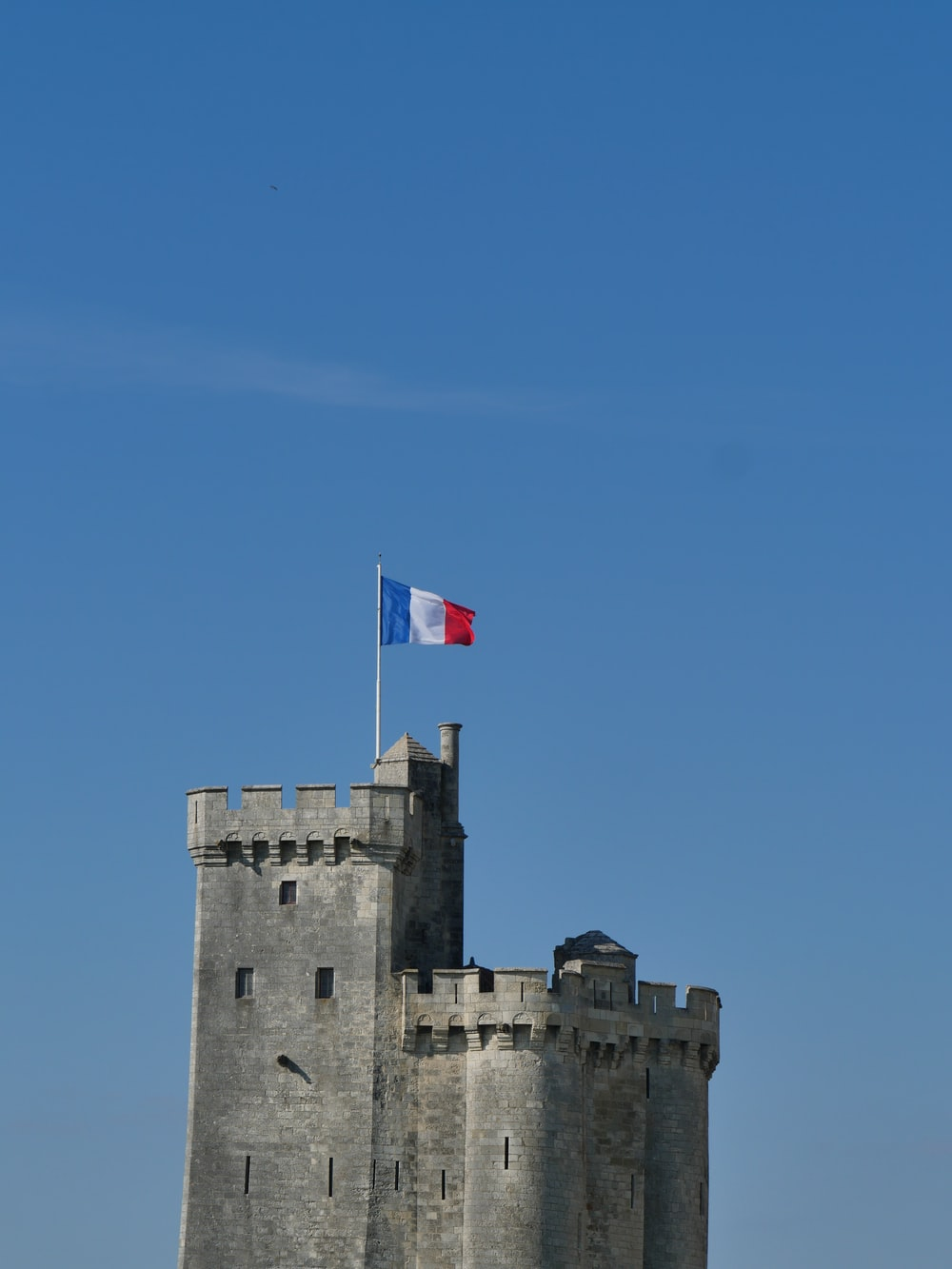 gray concrete castle with flag of us a on top under blue sky during daytime