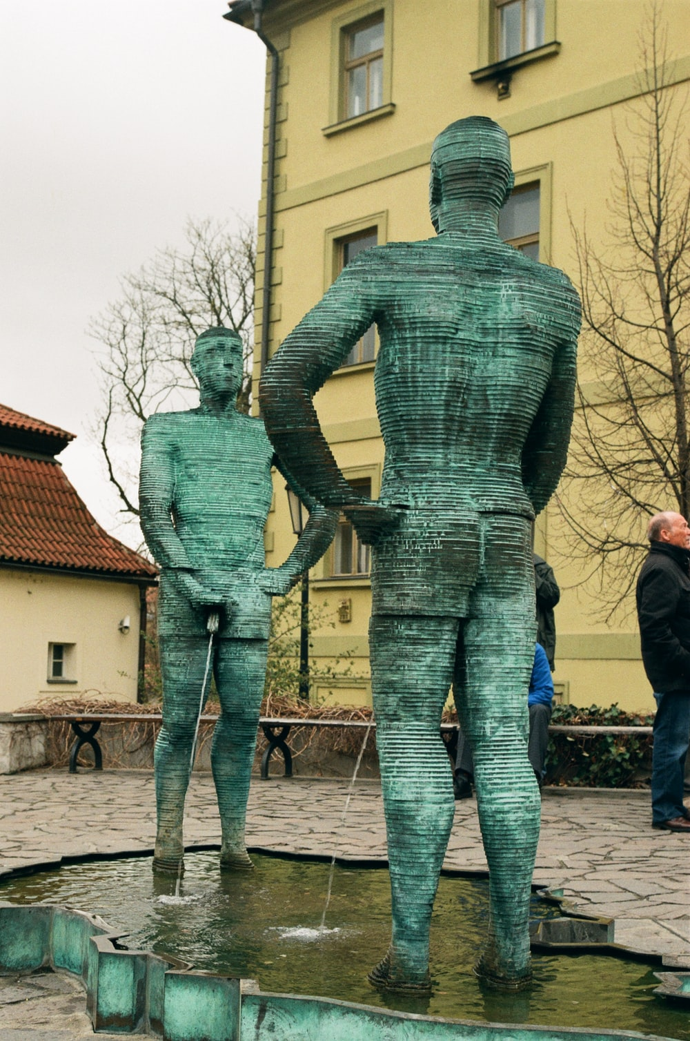 man in blue denim jeans standing beside statue