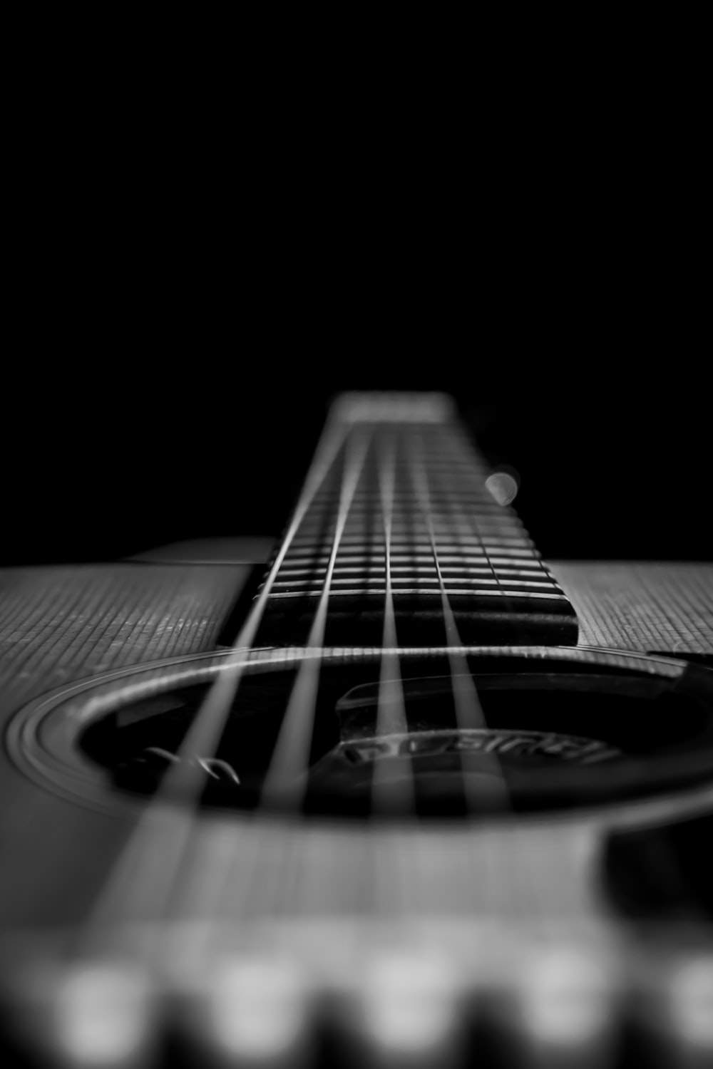 grayscale photo of acoustic guitar