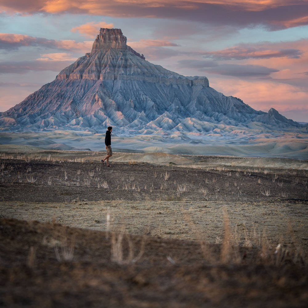 person standing on seashore near mountain during daytime