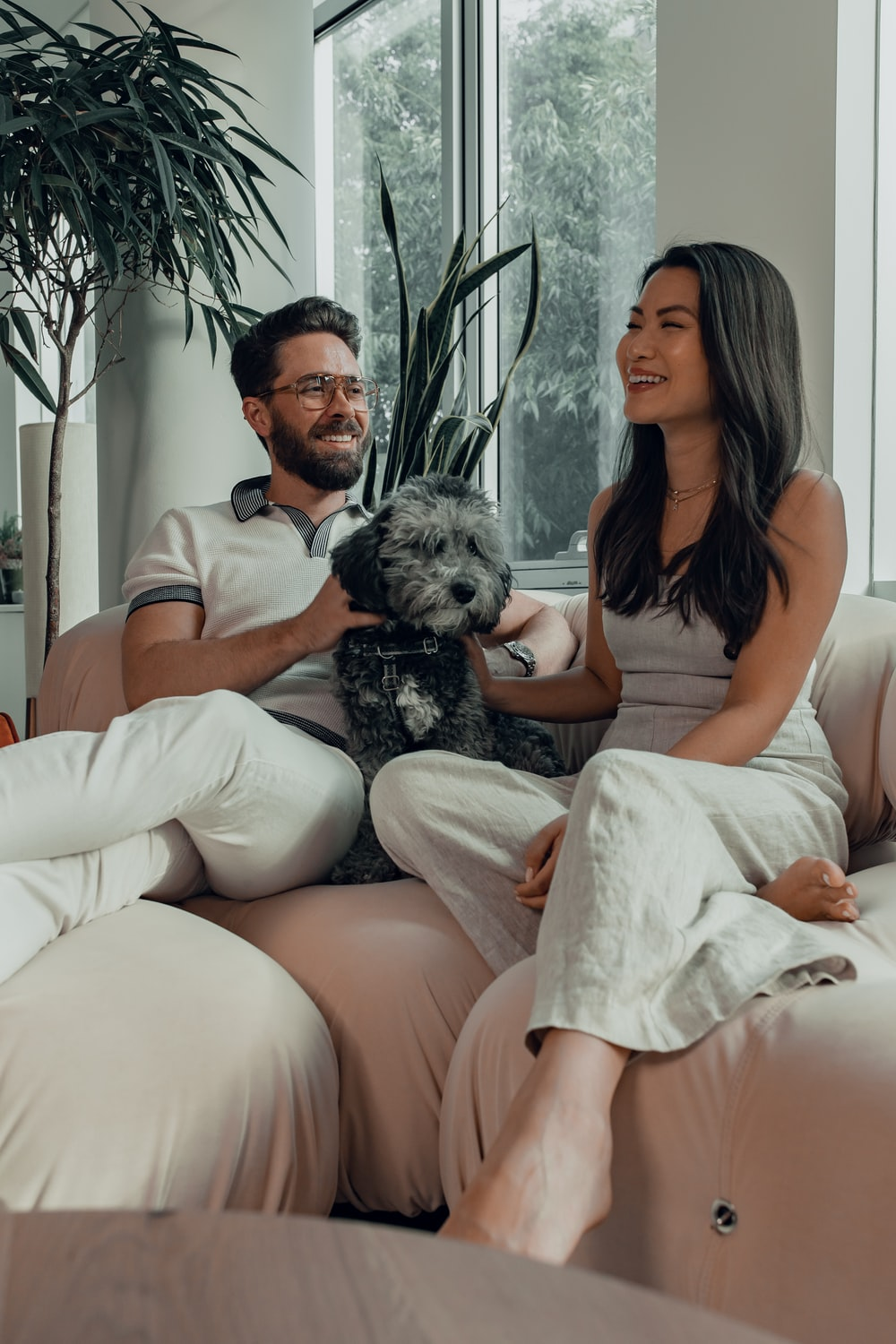 woman in black tank top sitting on couch beside man in white pants
