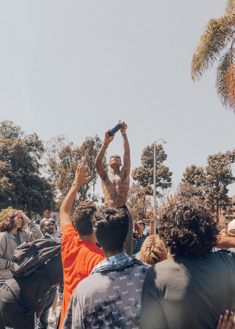 people standing and raising their hands during daytime