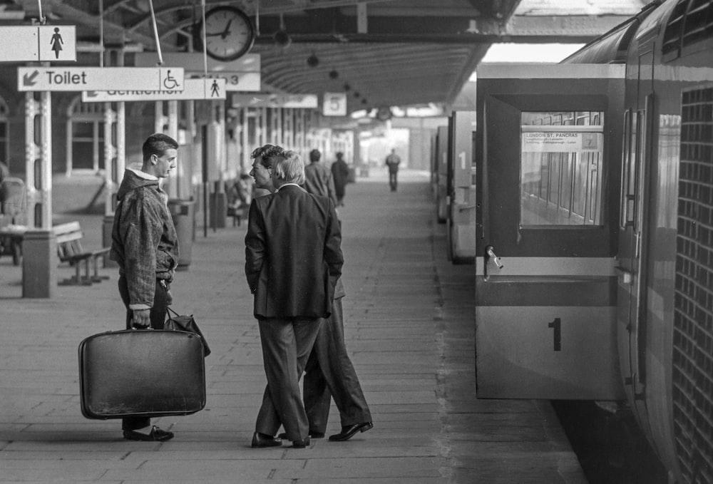 man in black coat walking on train station