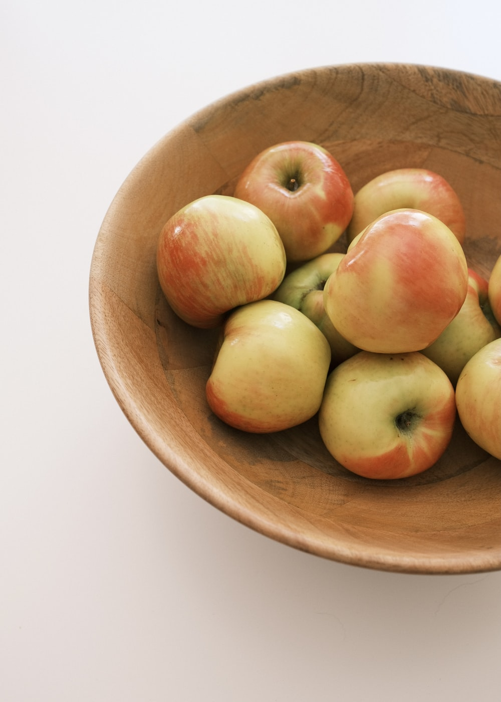 green and red apples on brown wooden bowl