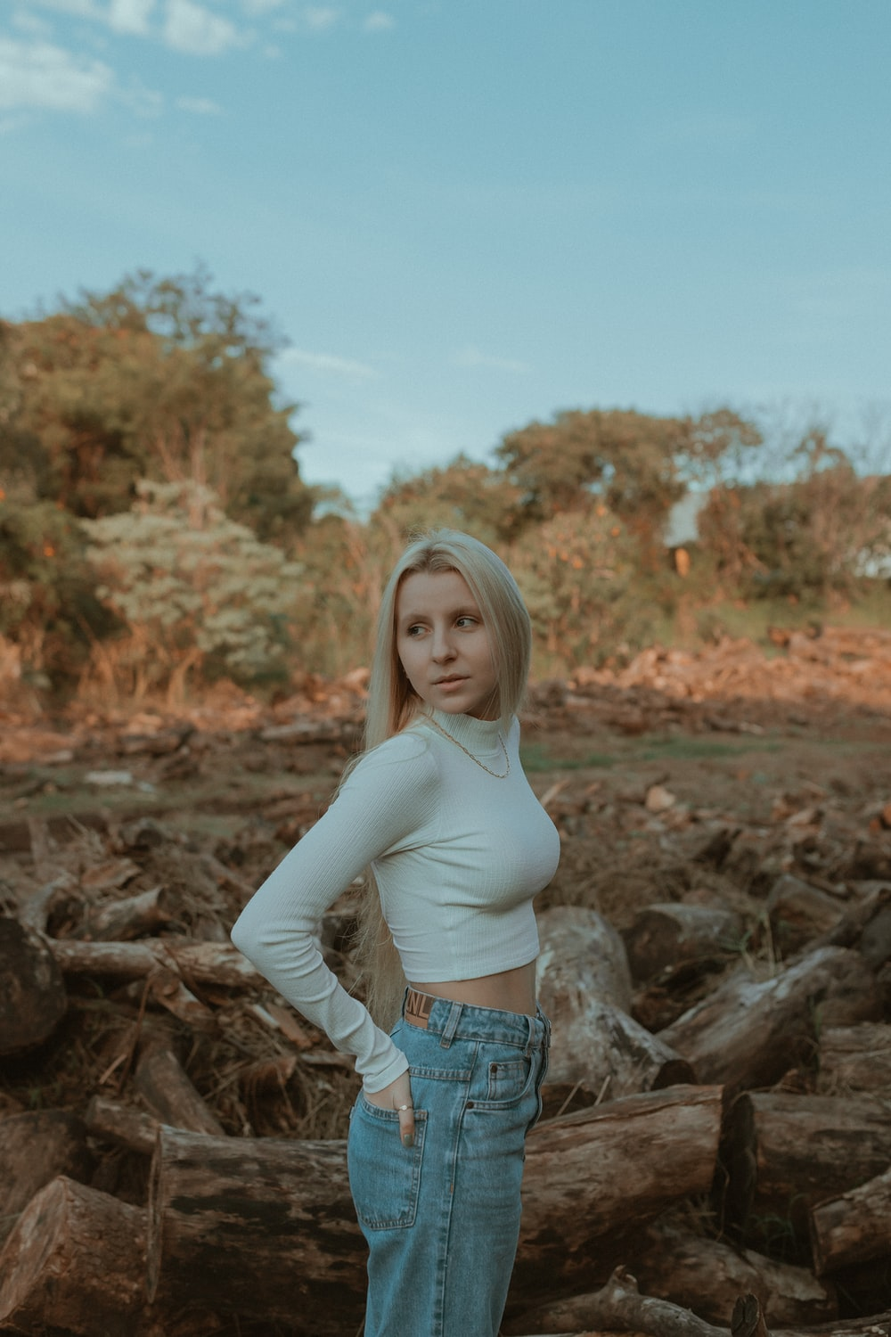 woman in white long sleeve shirt and blue denim shorts standing on brown rock during daytime