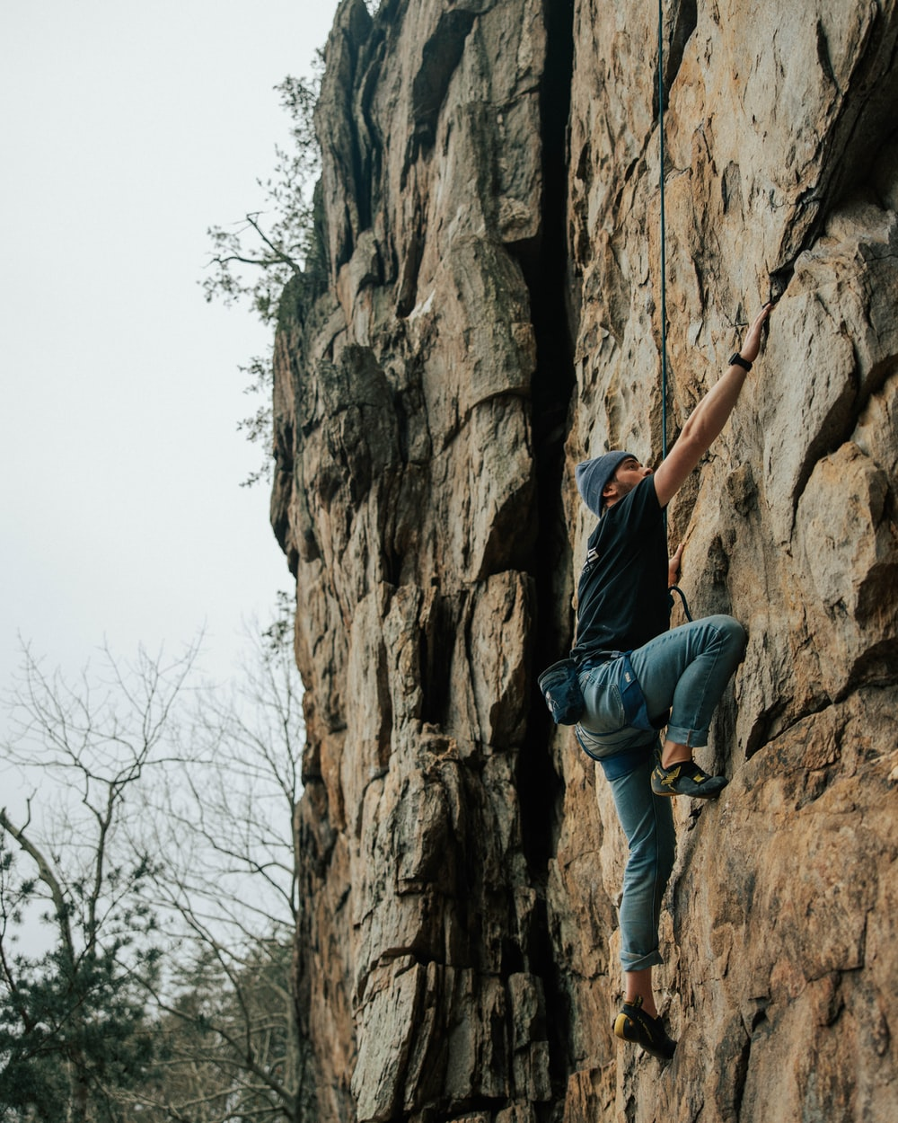 man in black t-shirt and blue denim jeans climbing on brown rock formation during daytime