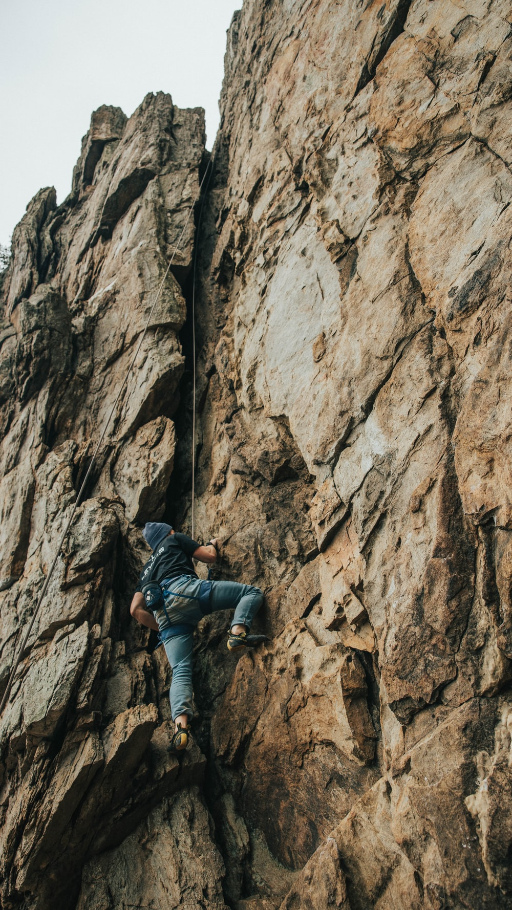 man in black jacket climbing on brown rocky mountain during daytime
