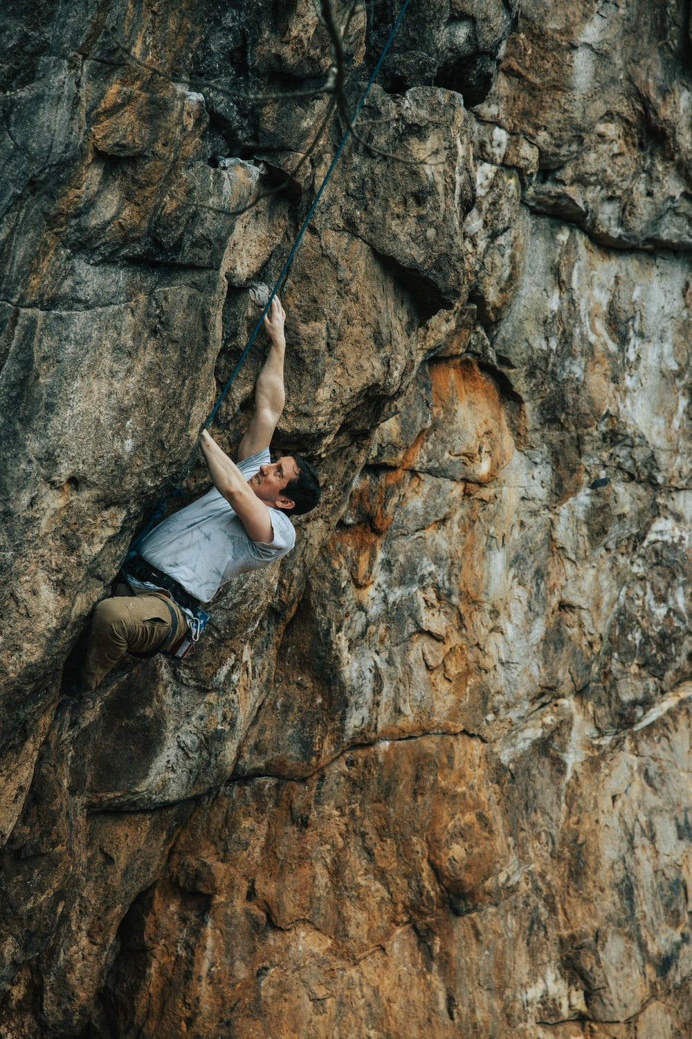 woman in gray tank top and black pants climbing on brown rock