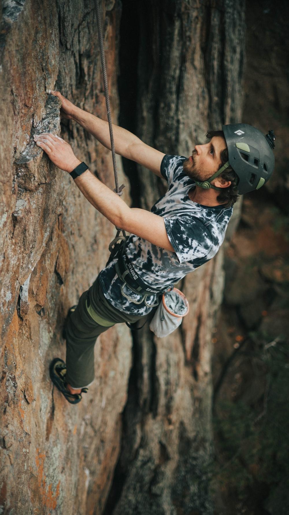 man in black helmet climbing on brown tree during daytime