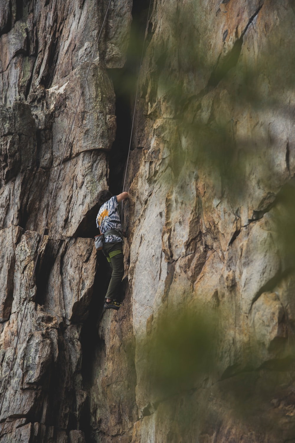 man in blue jacket climbing on brown rock formation during daytime