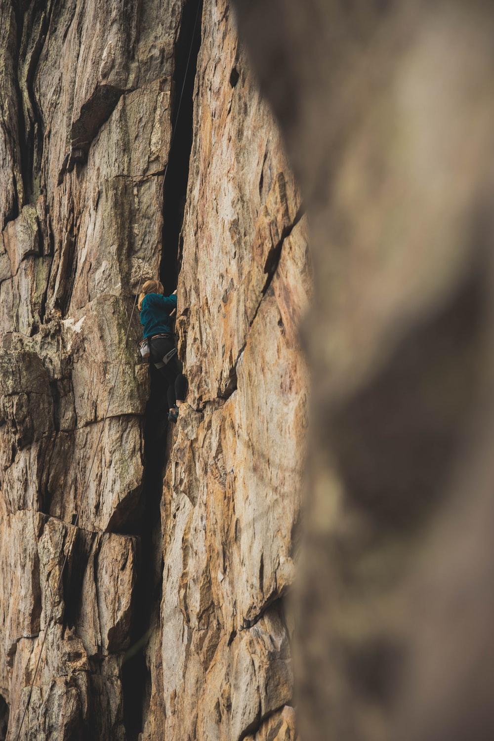 person climbing on brown rock