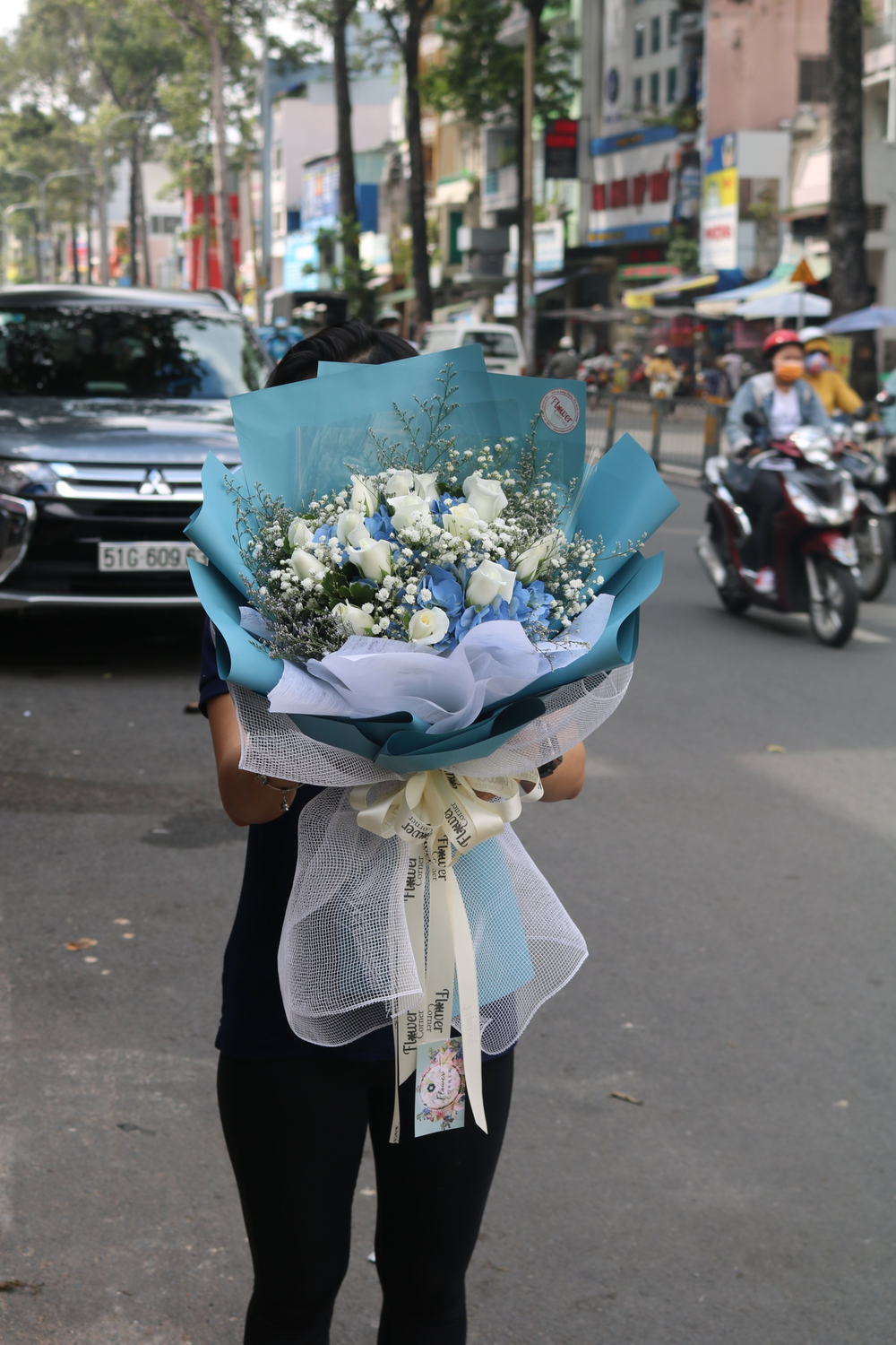 woman in black long sleeve shirt holding bouquet of flowers