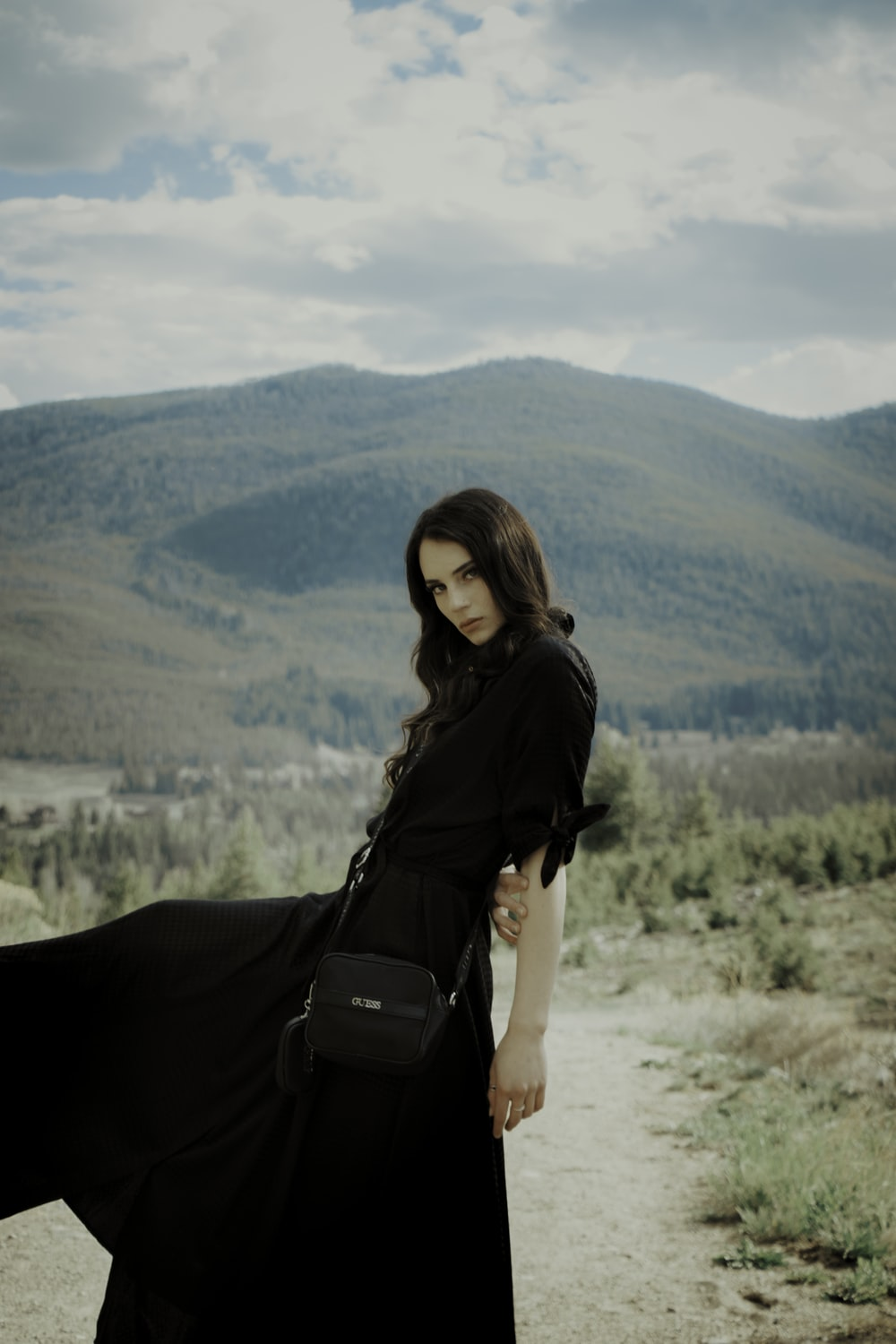 woman in black long sleeve shirt and black pants with black sling bag