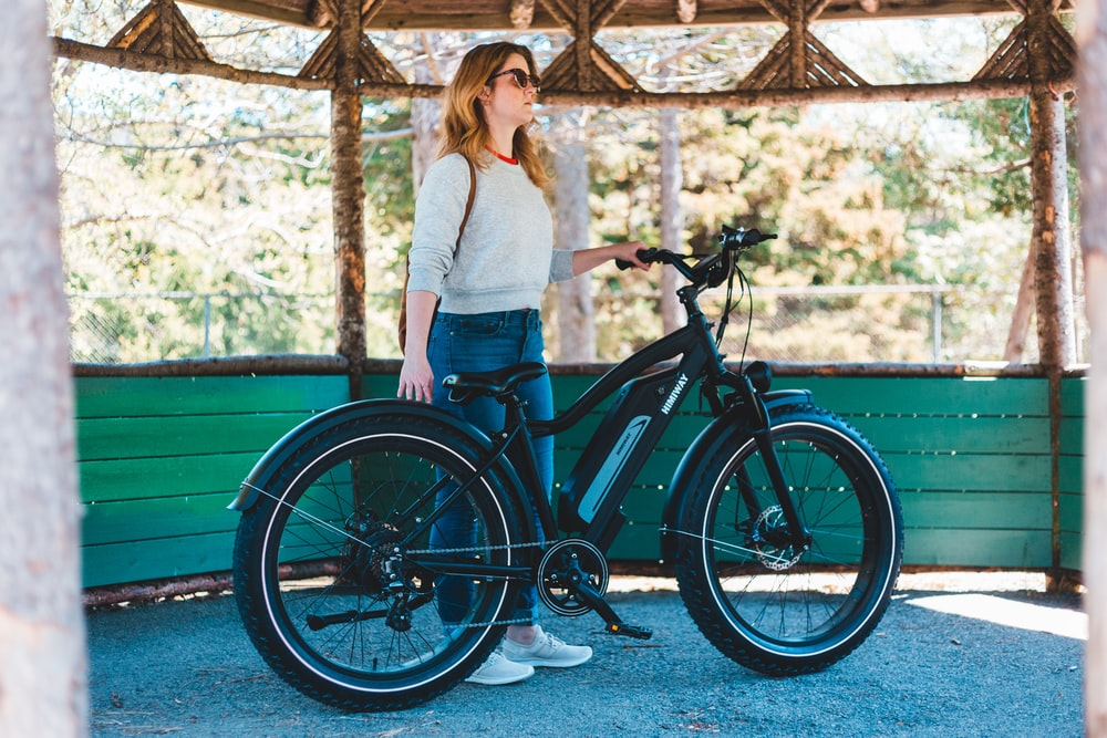 woman in white shirt and blue denim jeans standing beside black bicycle