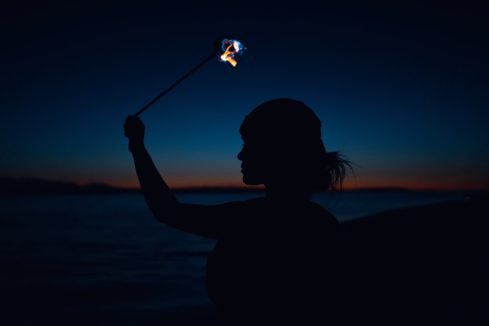 silhouette of woman holding sparkler during night time