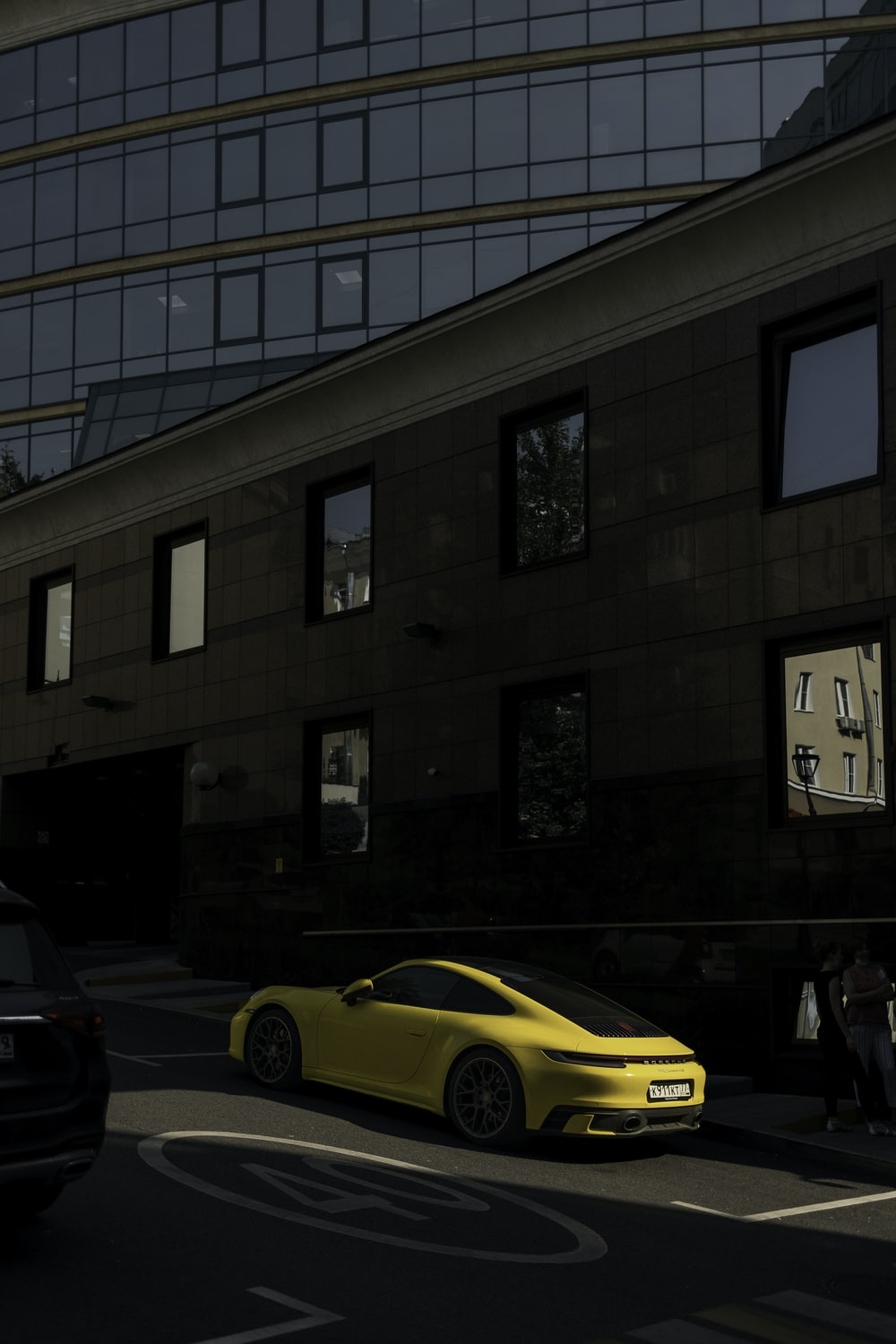 yellow car parked in front of brown building