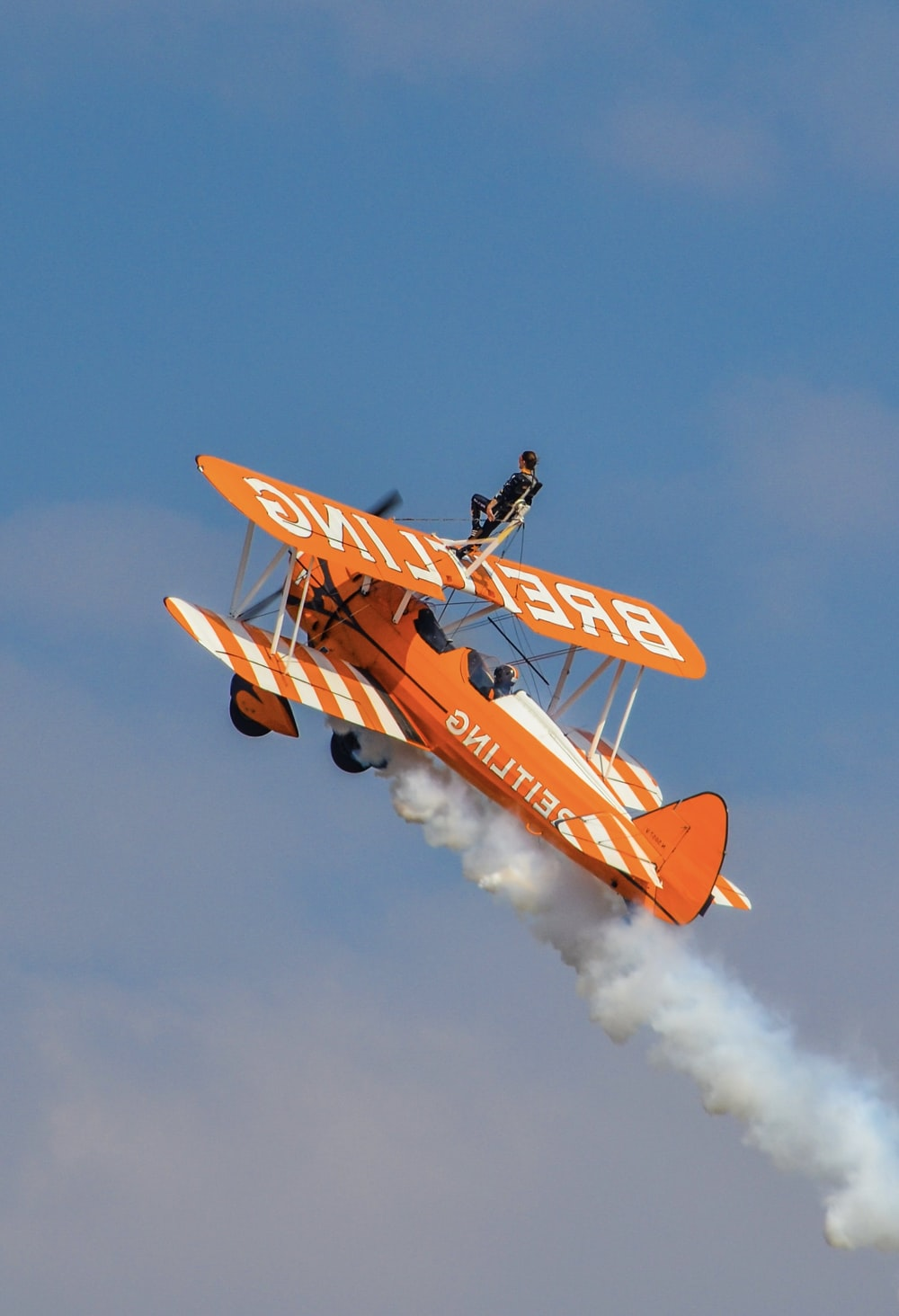 orange and yellow plane flying in the sky