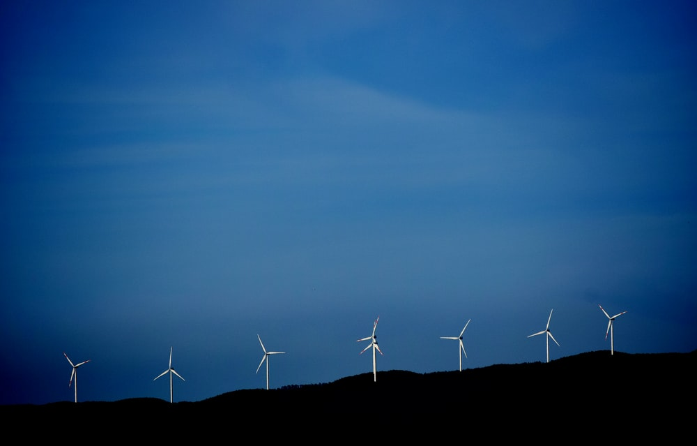 wind turbines on hill under blue sky