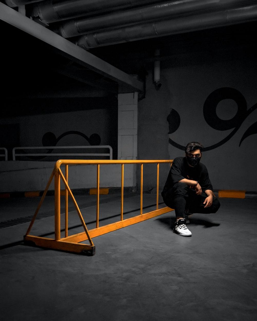 man in black jacket sitting on orange metal ladder