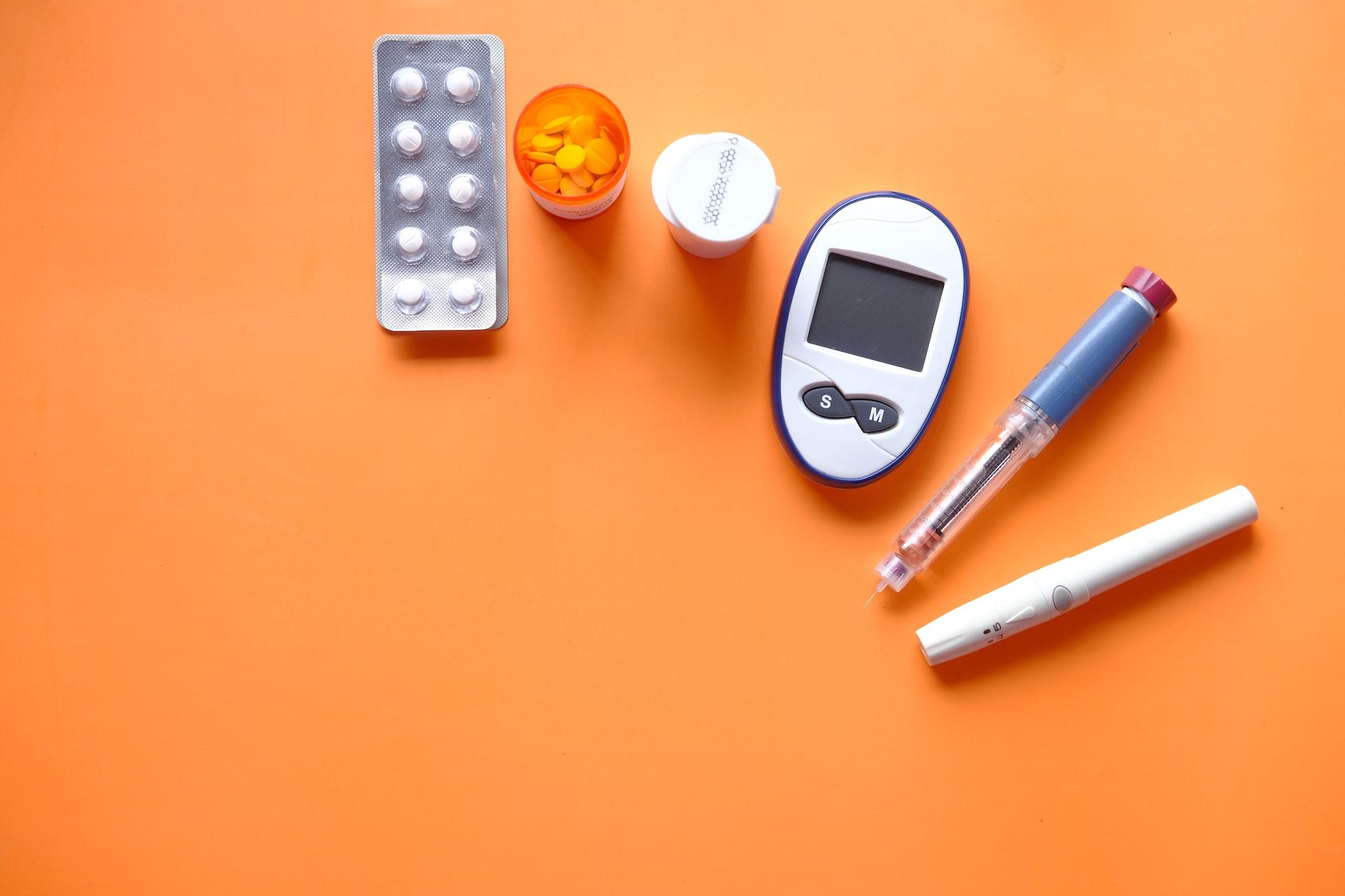 insulin pen, diabetic measurement tools and pills on orange background