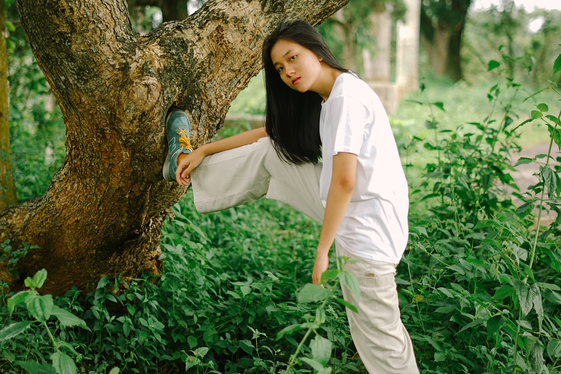 woman in white shirt and white pants standing beside tree
