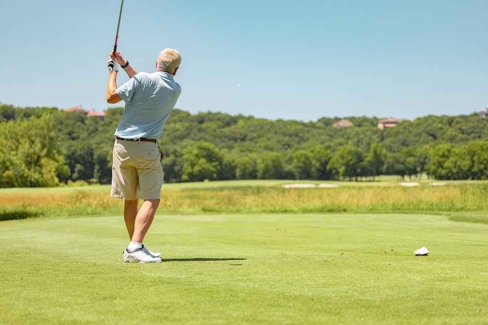 man in white t-shirt and brown shorts playing golf during daytime