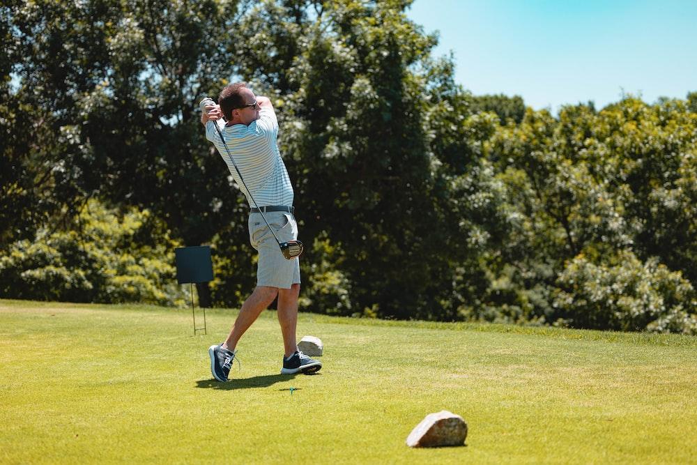 man in white and black stripe shirt playing golf during daytime
