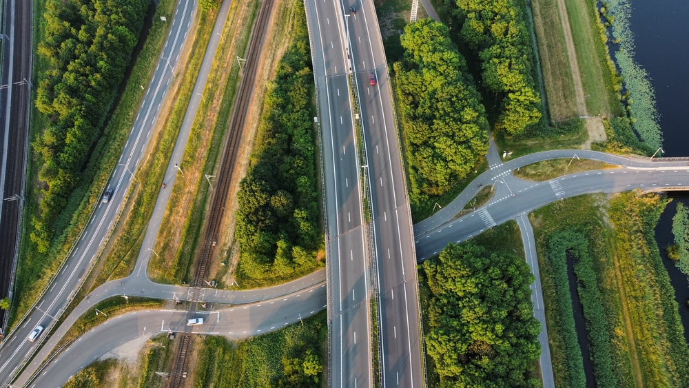 time lapse photography of cars on road between trees during daytime