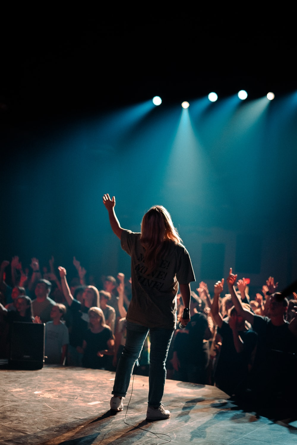 woman in black jacket standing on stage