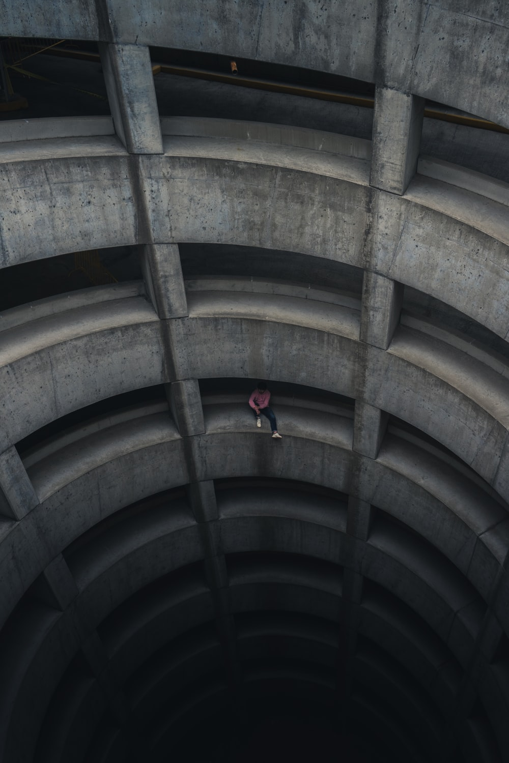 person in red jacket walking on brown tunnel
