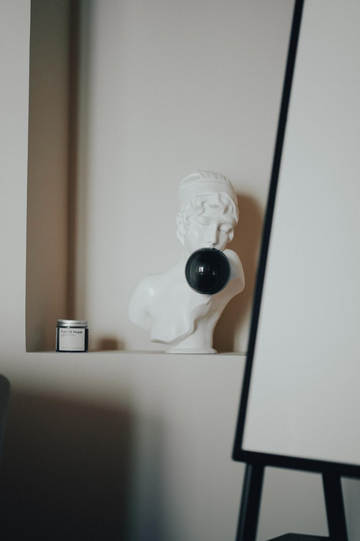 white ceramic figurine on white wooden shelf