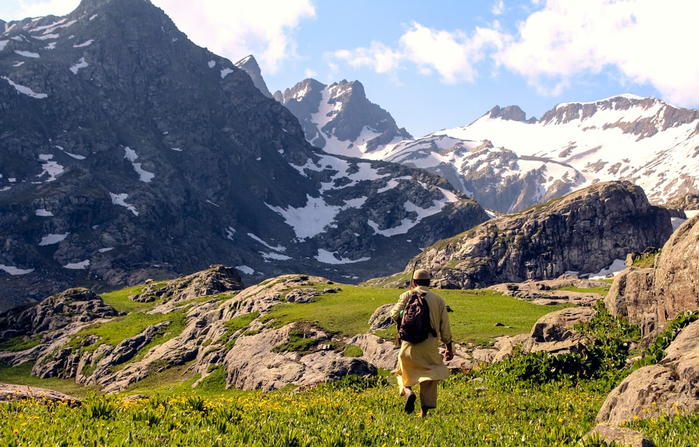 woman in brown shirt sitting on green grass field near snow covered mountains during daytime