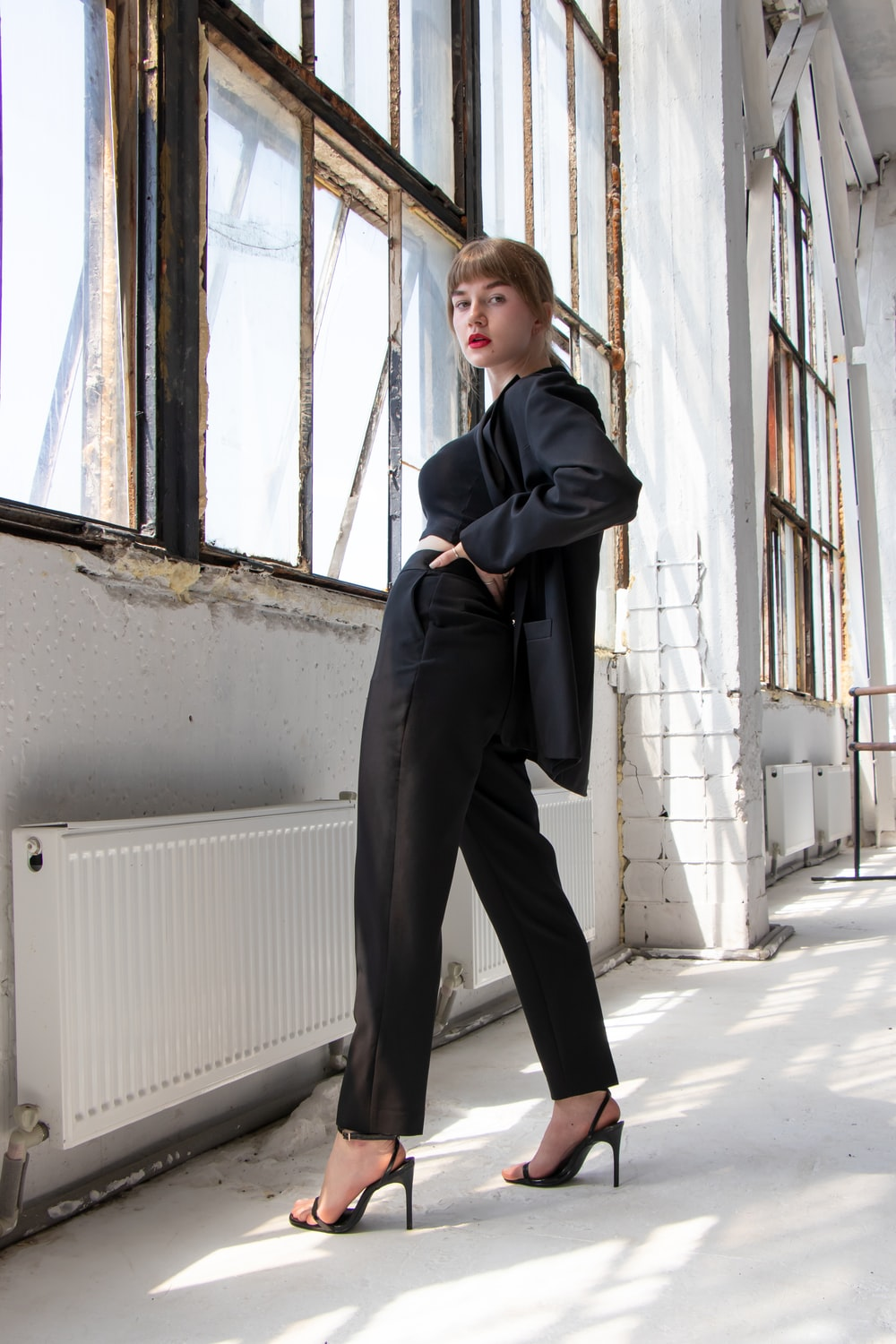 woman in black blazer and gray pants standing beside window during daytime