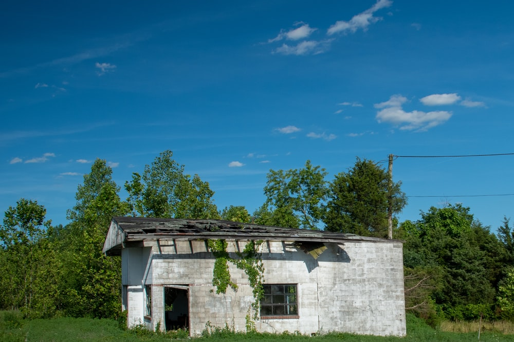 white concrete house near green trees under blue sky during daytime