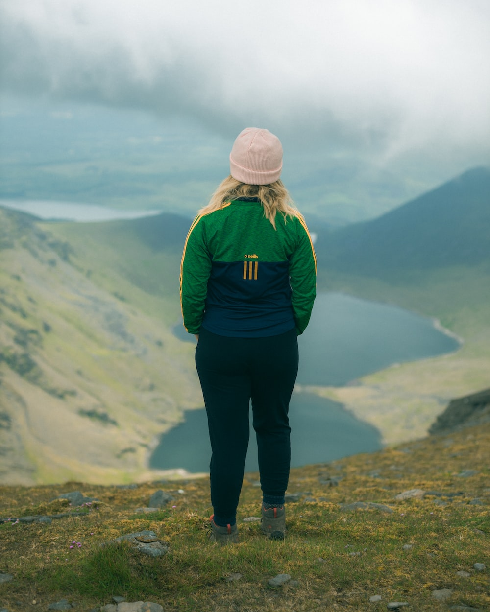 woman in green jacket standing on top of mountain during daytime
