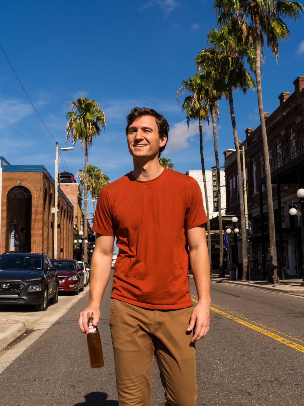 man in blue crew neck t-shirt and brown pants standing on sidewalk during daytime
