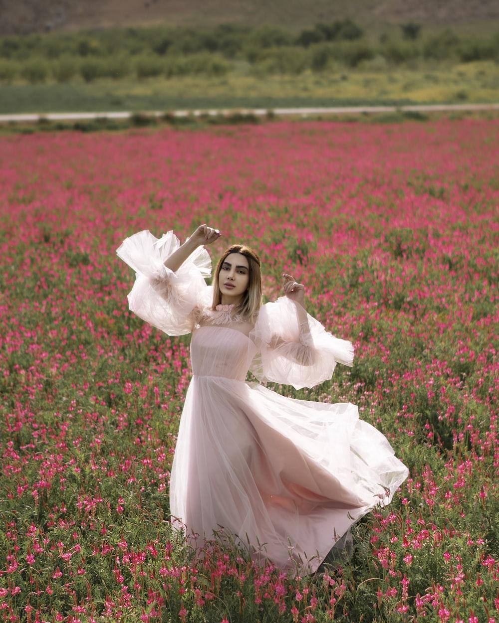 girl in white dress lying on red flower field during daytime