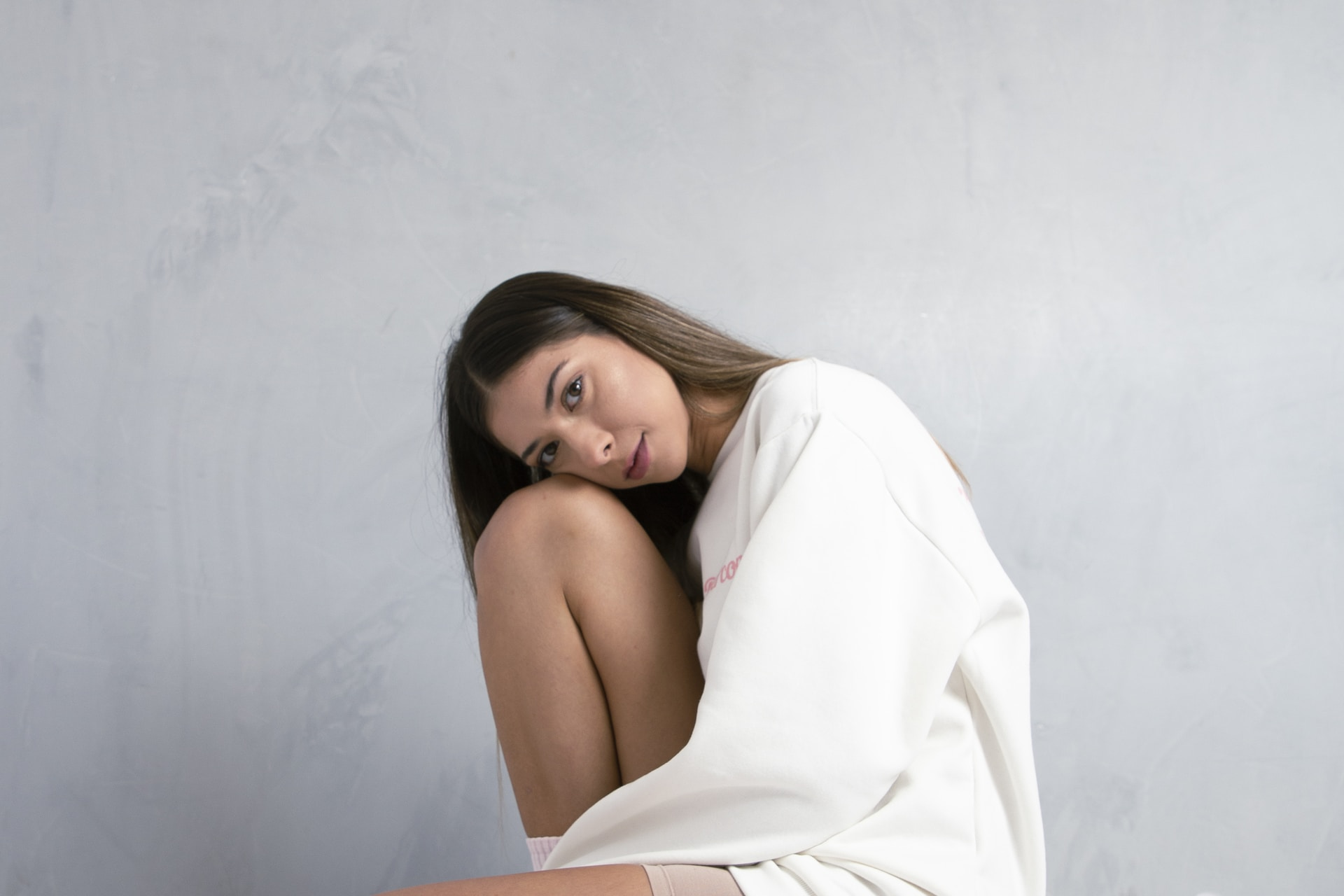 woman in white long sleeve shirt leaning on white wall