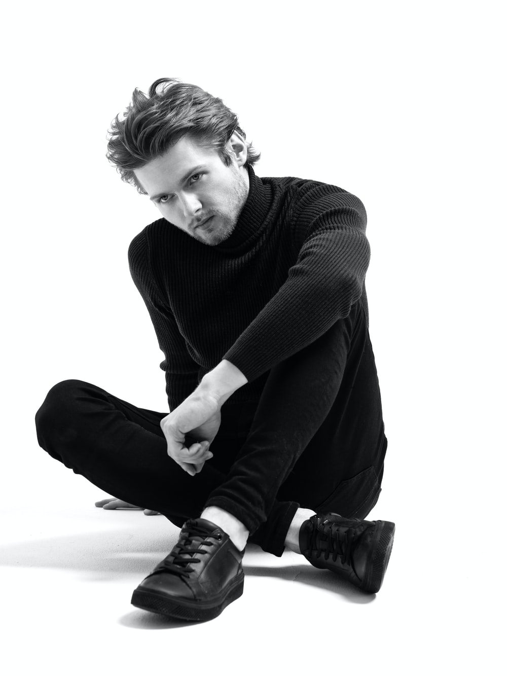 man in black sweater and black pants sitting on floor