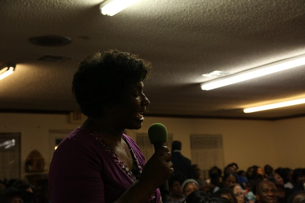 woman in purple dress holding microphone