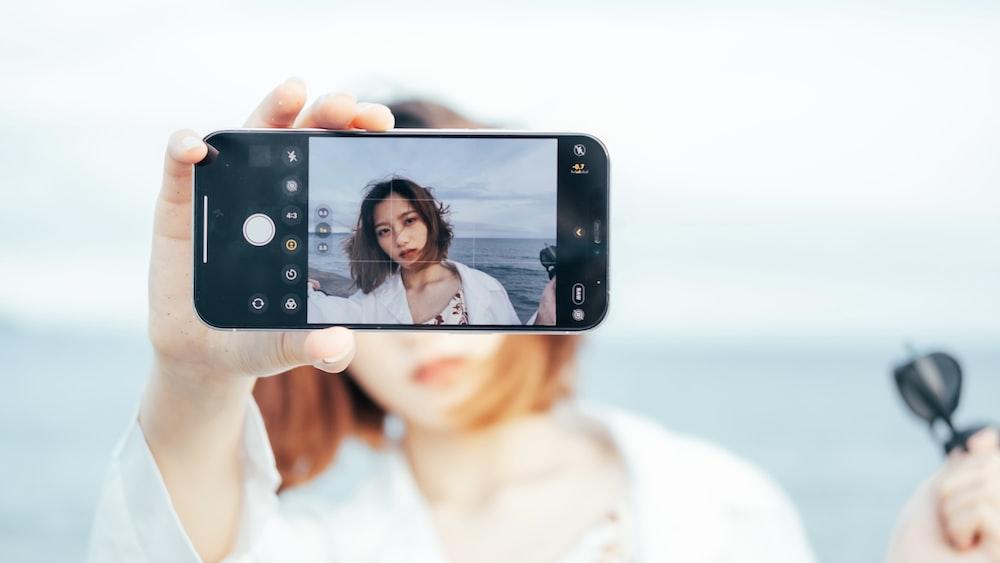 woman in white tank top holding black smartphone taking selfie