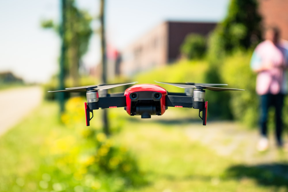 red and black drone in mid air during daytime